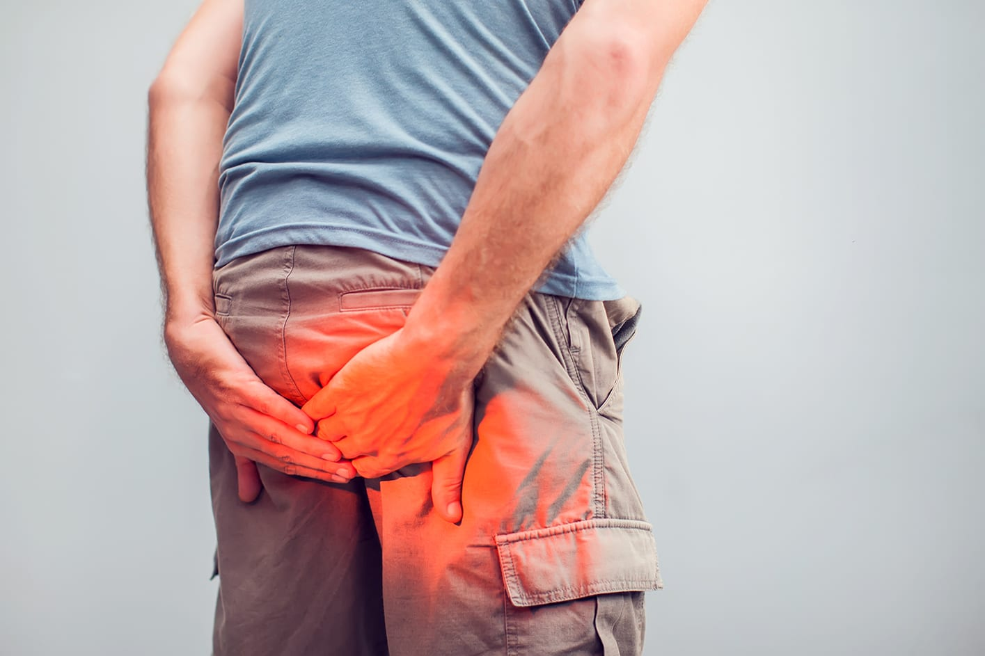 Man with hemorrhoids holding his butt in pain, in a white background